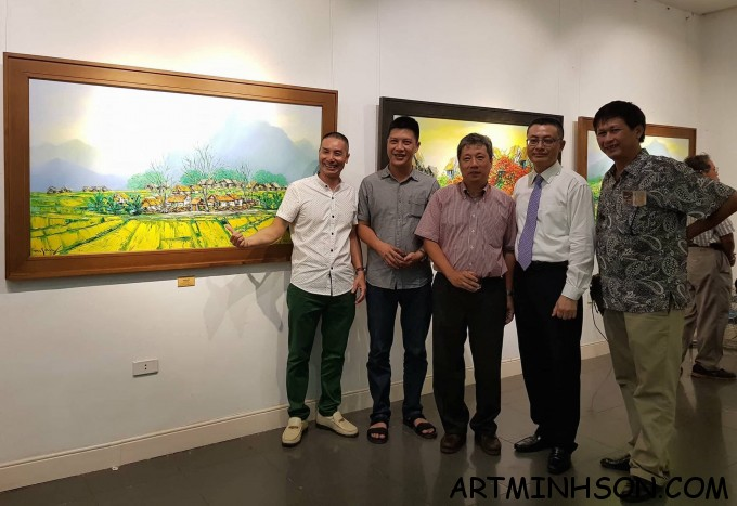 """Painter Nguyen Minh Son is introducing his """"Vietnam landscape painting"""" to the guests."""